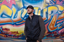 man standing in front of a wall covered in graffiti