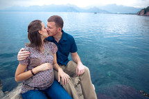 man and pregnant woman kissing sitting on a rock in front of the ocean