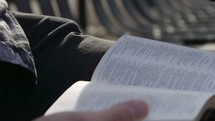 man reading a Bible on a bench