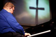 man playing a piano at a worship service