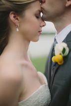 groom tenderly kissing bride