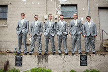 groomsmen standing on a concrete wall