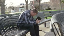 a man sitting on a bench praying holding a Bible