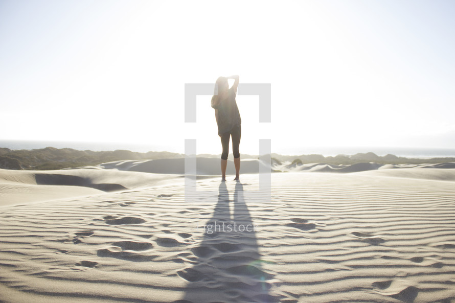 a woman standing in sand casting a shadow