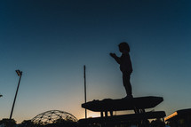 silhouette of a child standing on a picnic table at sunset