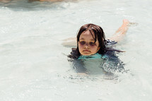 a little girl wadding in shallow pool water