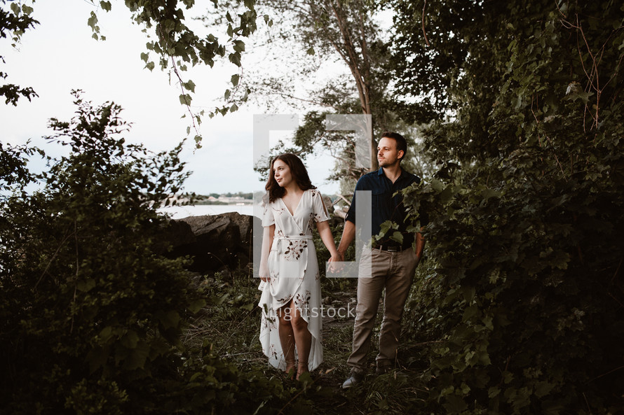 a couple holding hands in the woods by a shore