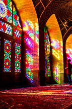 colors from stained glass windows shining on a rug in a mosque