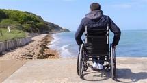 man in a wheelchair on a beach shore