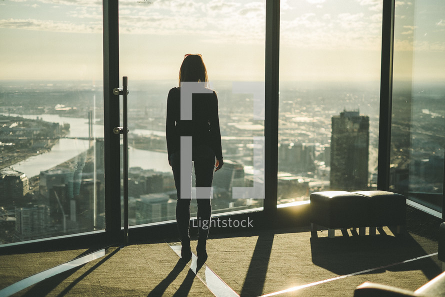 A woman looks out a wall of windows over a large city.