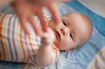 Infant lying on blanket reaching up for hand.