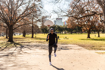 A man in workout clothes exercising in a park.