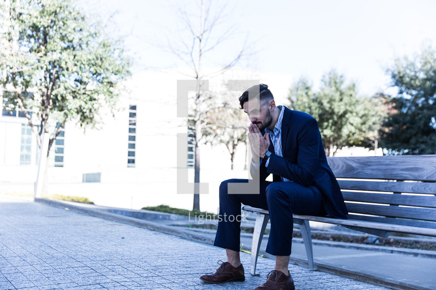 a man sitting on a bench in prayer