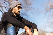 A man in workout clothes sits outdoors.