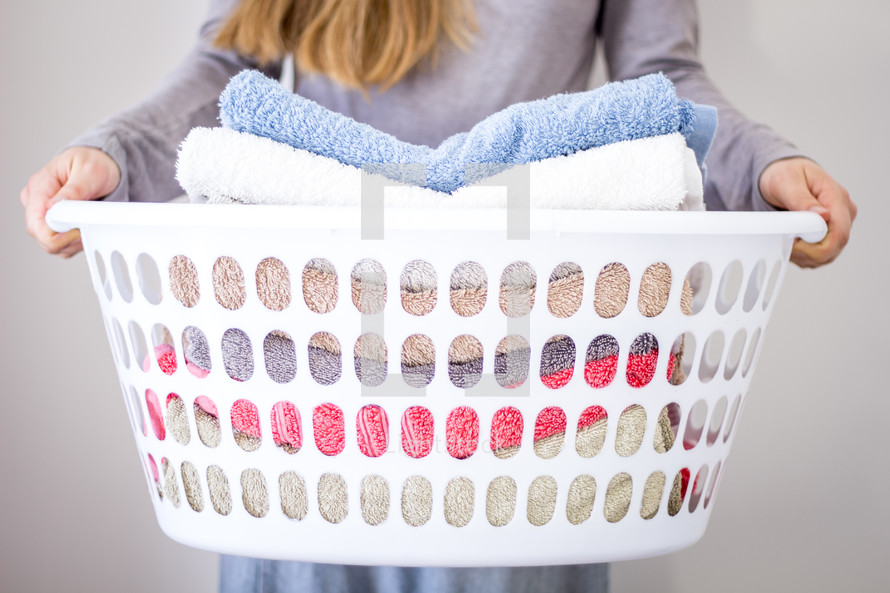 Lady holding washing basket with towels