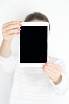 a woman holding up an iPad