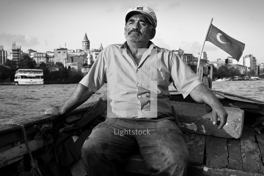 Turkish, Turk, Muslim, man in boat on Bosphorus Strait with Galata Tower in background, Turkish flag