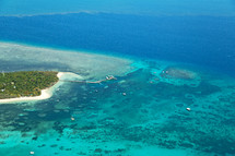 aerial view over island and coral reef
