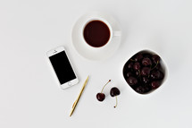 iPhone, pen, cherries, and coffee cup