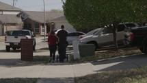 a couple walking on a sidewalk pushing a stroller