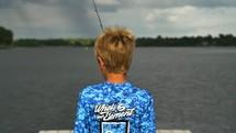 a boy child fishing off a dock