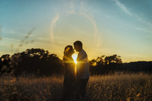 a couple standing together in a field at sunset