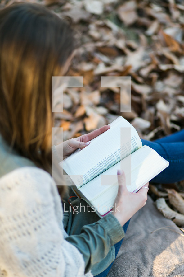 a woman reading from a Bible in her lap