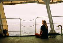 A woman sitting on a ferry looking out at the water