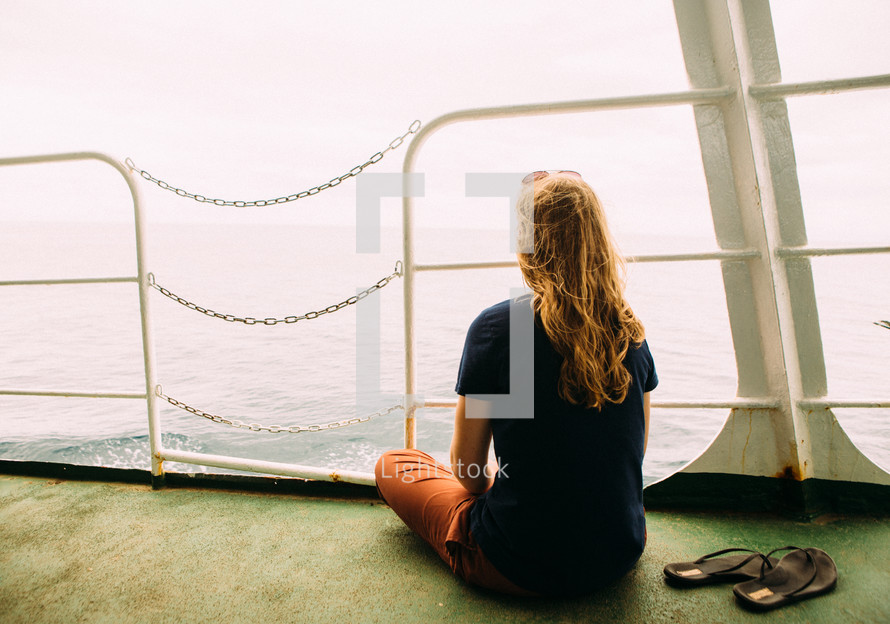 a woman looking off the back of a ferry