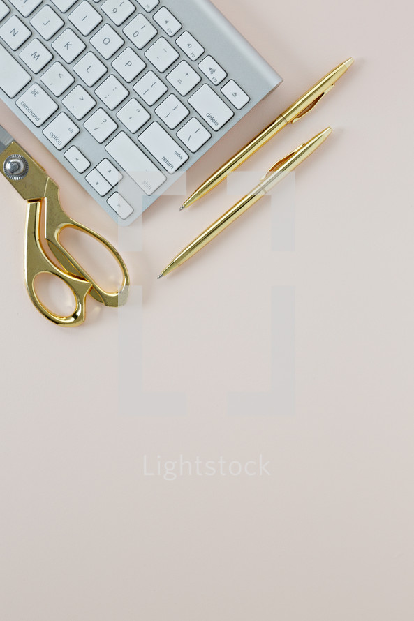 gold scissors, gold pens, and computer keyboard on a pink background