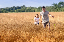 children running in a field of wheat