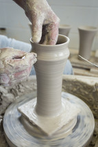 potter shaping a tall vase