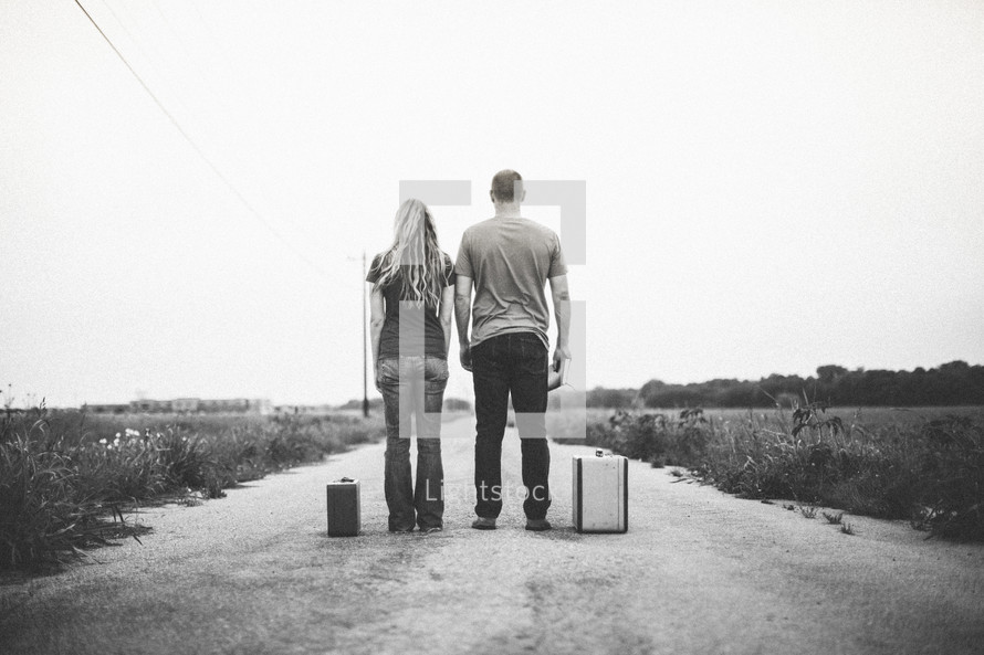 Couple standing in the middle of a dirt road with suitcases and a Bible.