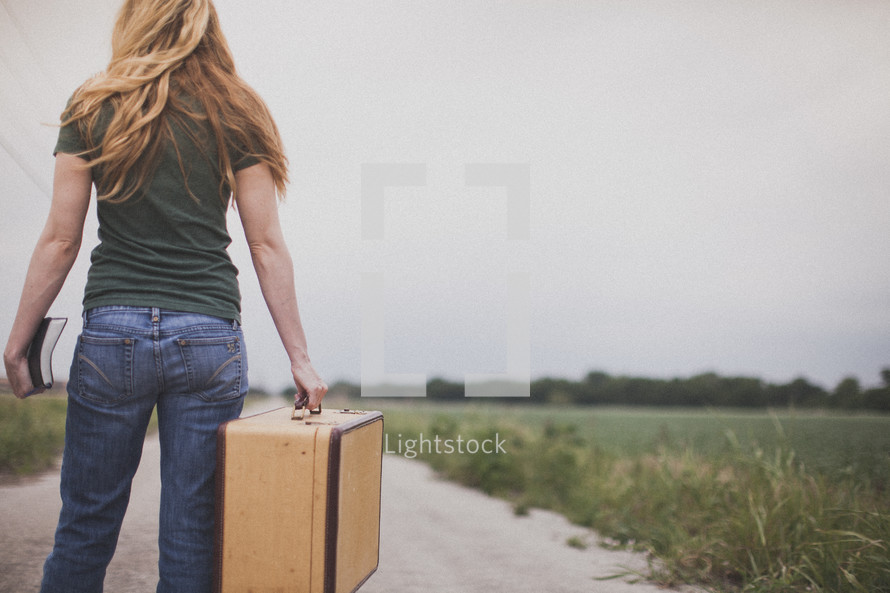woman carrying a suitcase and holding a Bible