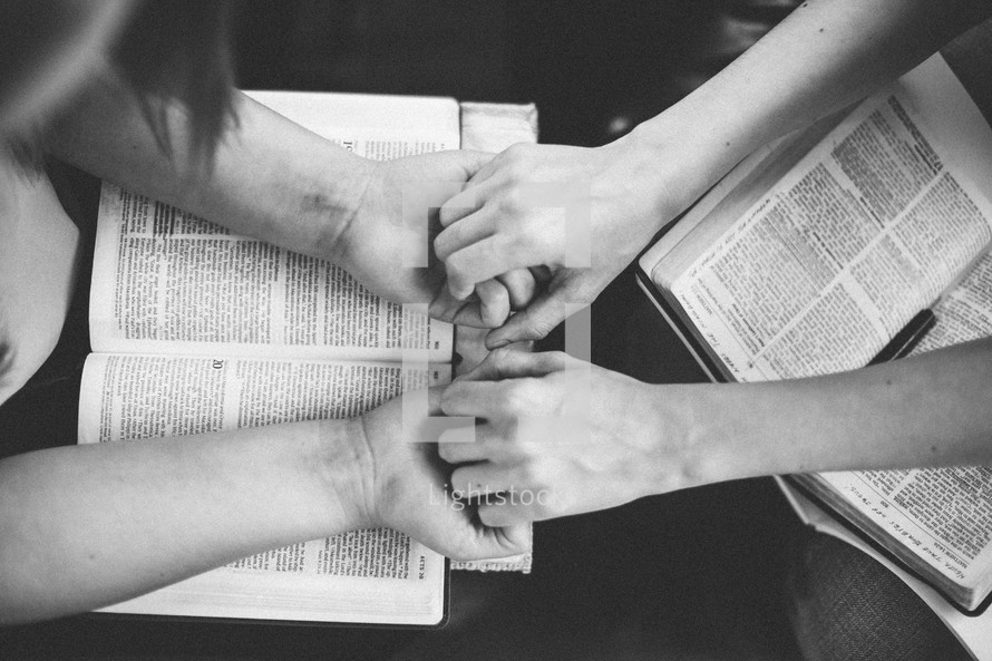 woman holding hands in prayer over a open Bible