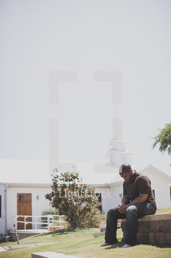 man praying outside in front of a church