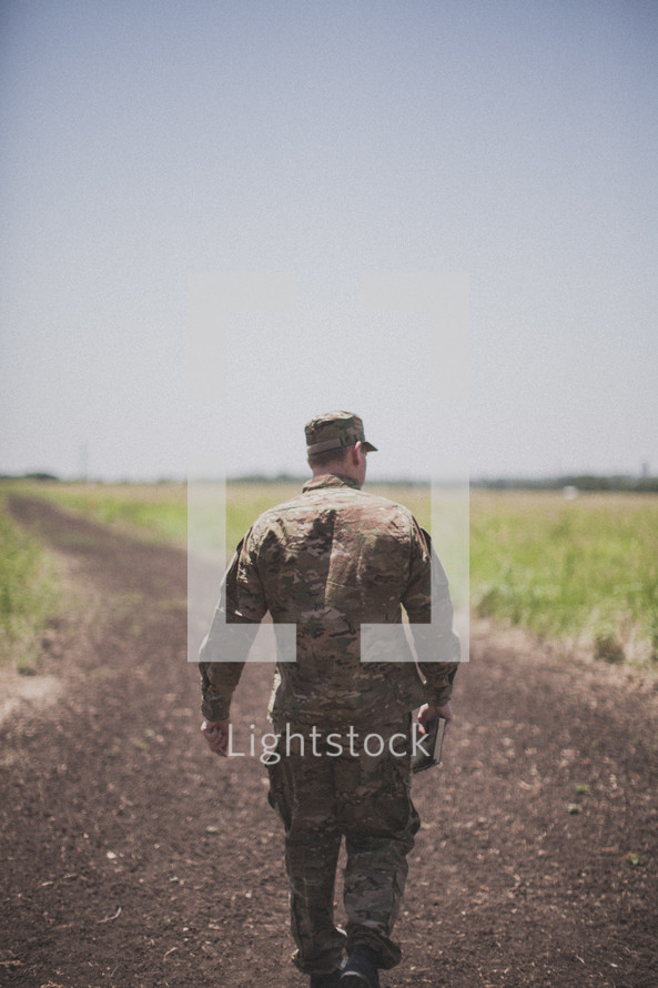 serviceman walking down a dirt road