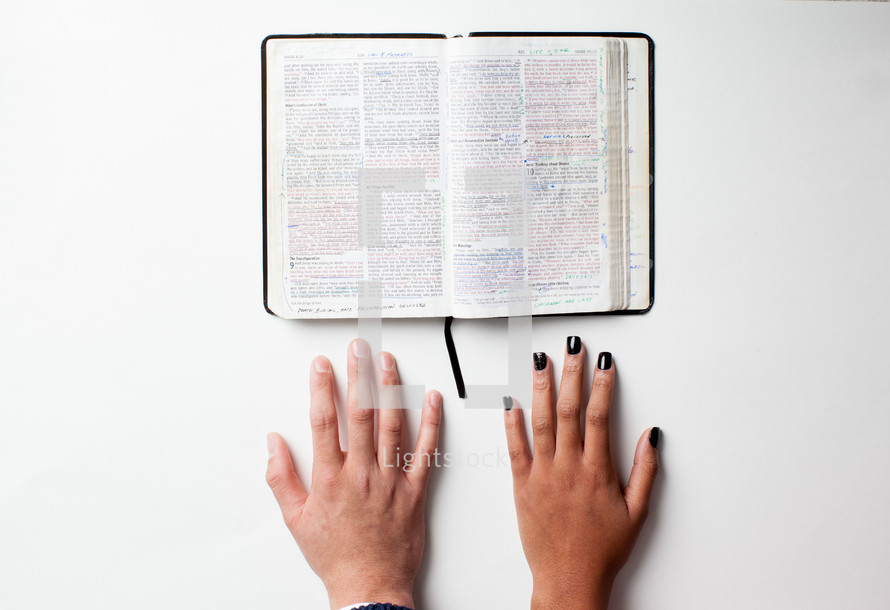 open Bible and hands on a table