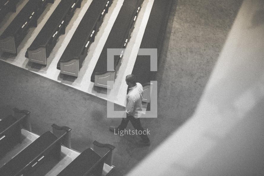 man walking down the aisle of an empty church