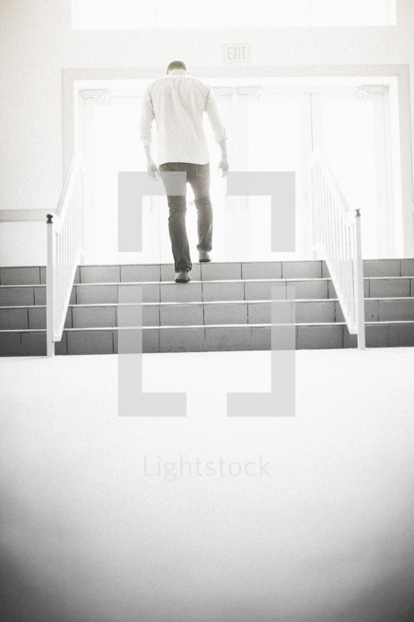 man walking up stairs exiting a church
