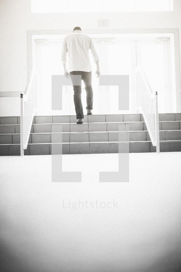 man walking up stairs exiting a church