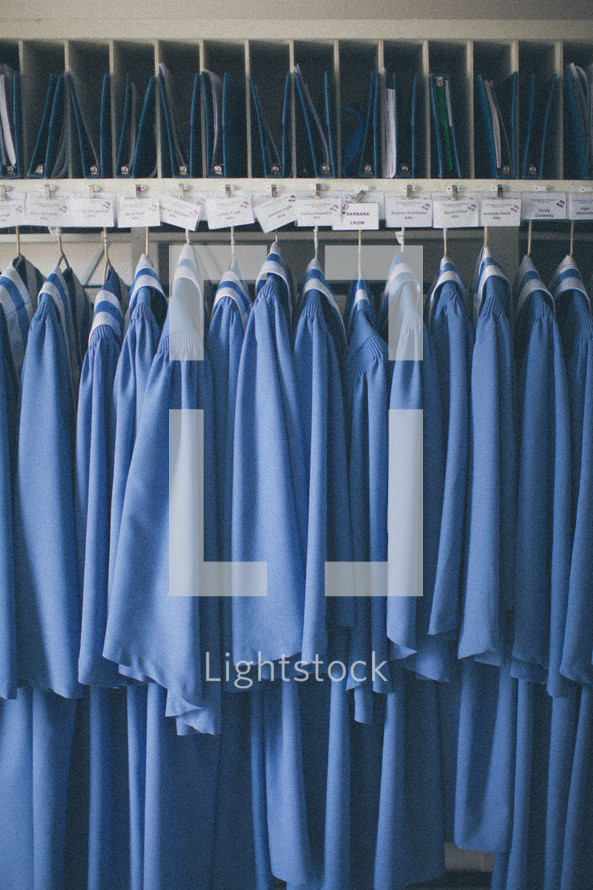 Choir robes hanging in a closet.
