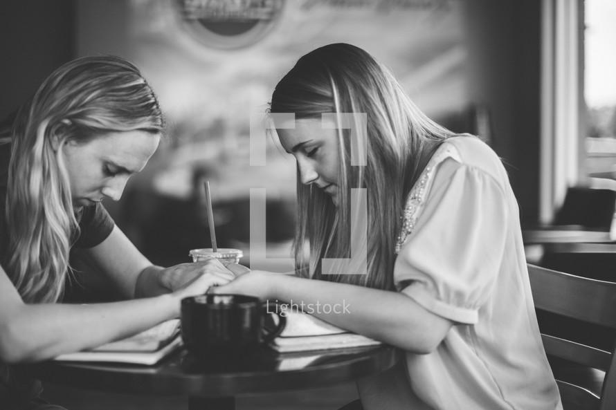 women holding hands in prayer over Bibles