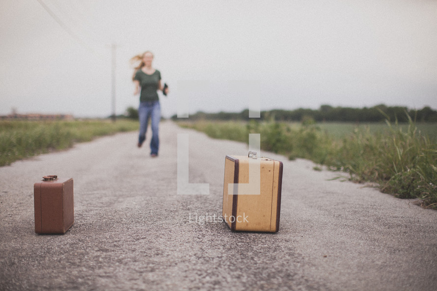 woman running down a road towards suitcases