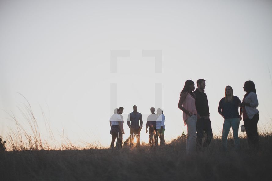 groups of people standing around talking outdoors in a field