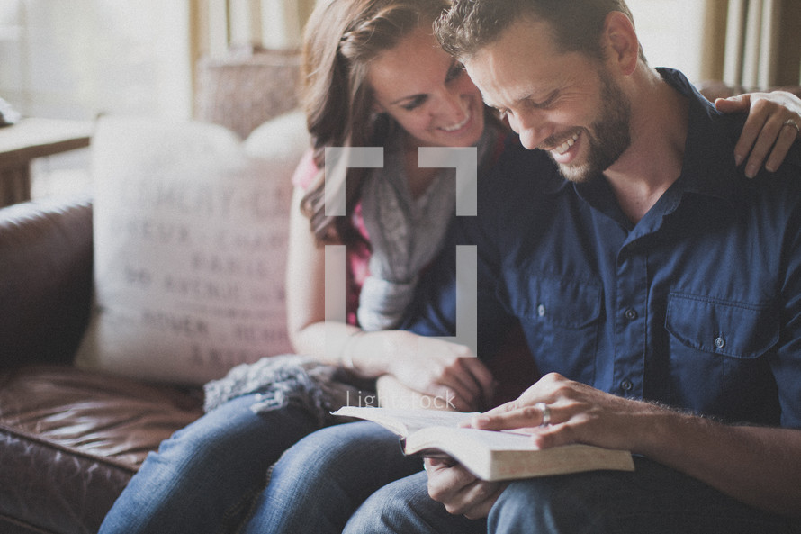 husband and wife reading a Bible together