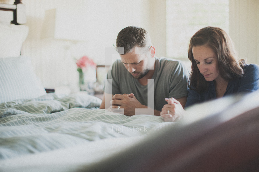 husband and wife praying together at the edge of a bed