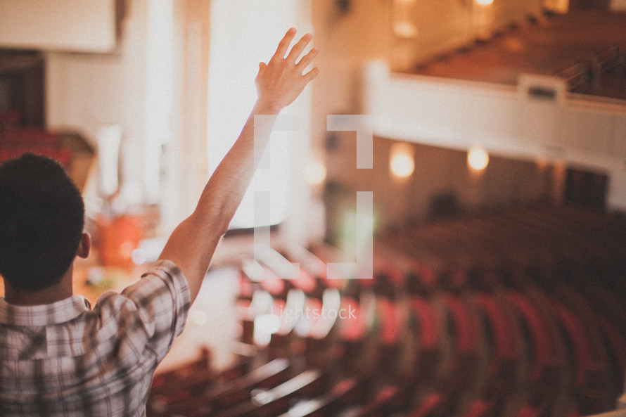 man with his hand raised in worship in a church