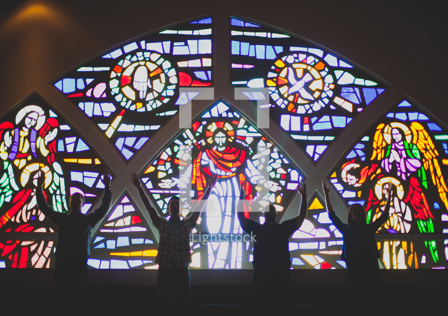 Silhouette of people with arms raised standing front of a stained glass window.