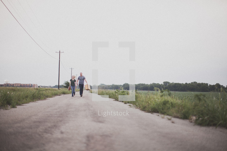 Couple carrying suitcases walking in the middle of a dirt road.